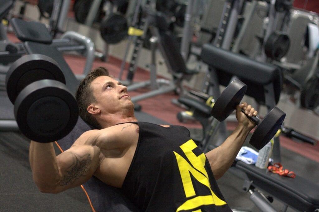 Mand træner med håndvægte i center