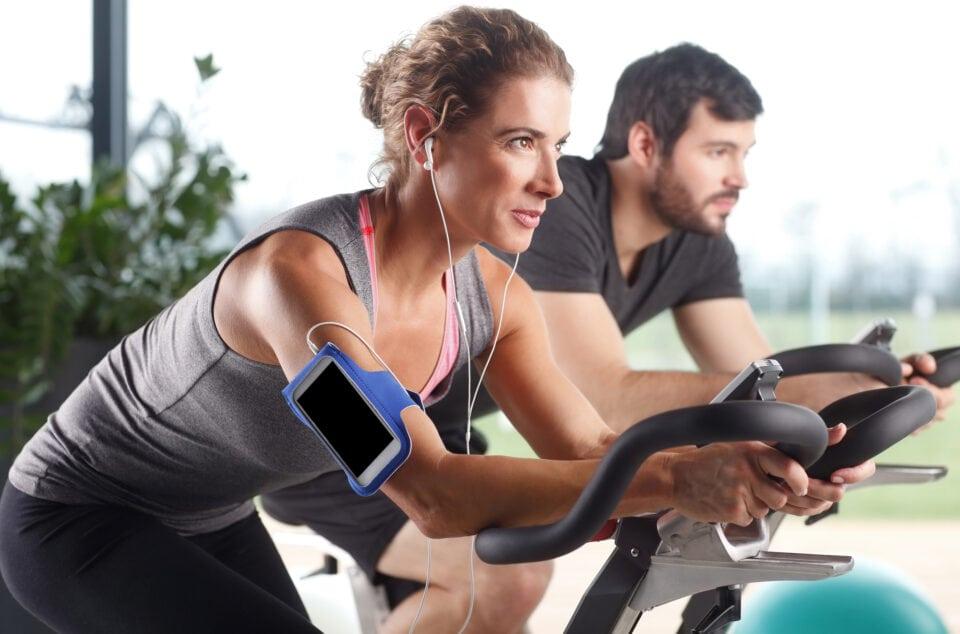 mand og kvinde på spinningcykler ser koncentrerede ud